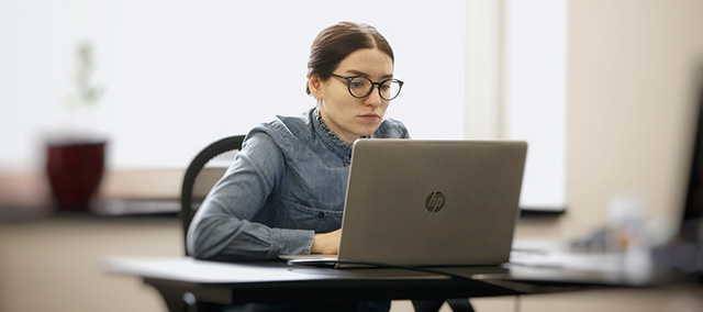 Woman's hand on mouse, computer work space